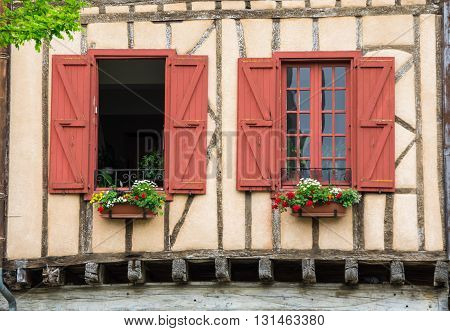Windows of old framework houses at main square of medieval village Mirepoix in southern France