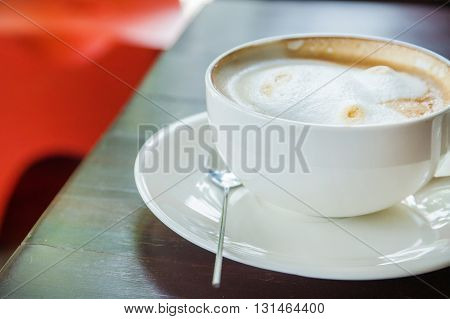 coffee with spice and artistic foam in a white cup.
