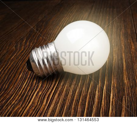 Glowing light bulb close-up on a wooden background