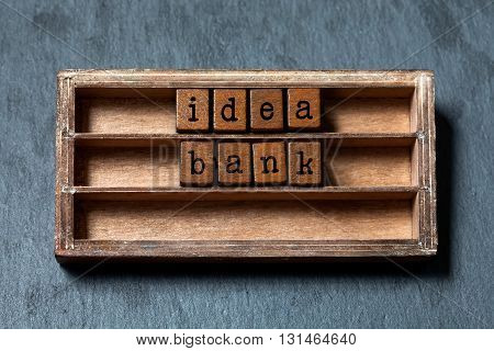 Idea bank concept image. Vintage shelf with blocks text letters, aged wooden box. Gray stone background, macro