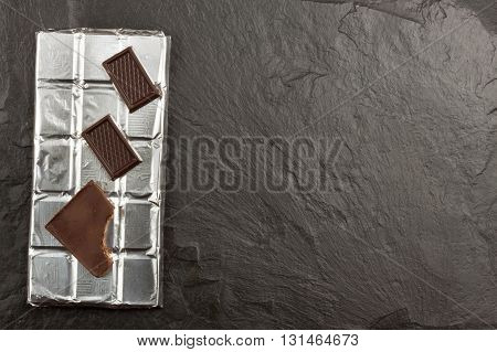 Chocolate wrapped in aluminum foil on dark slate. Advertising on chocolate. Sales chocolate . Packing chocolate. Chocolate shop. Sweet chocolate bar.