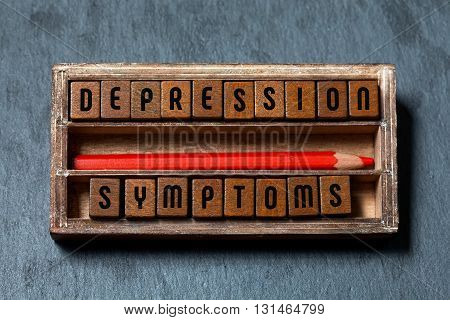 Depression symptoms conceptual image. Vintage box with textured wooden blocks letters text, red pencil. Gray stone background, macro view