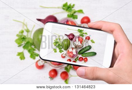 Hands taking photo tomato salad with cucumber and feta with smartphone.
