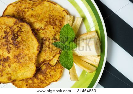 Delicious banana pancakes on a plate with green mint