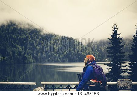 Young woman relaxes on the background of the lake with the mountains. Hiking and backpack resting. Travel Lifestyle concept Summer journey vacations outdoor mountains on background. Satisfied happy girl.