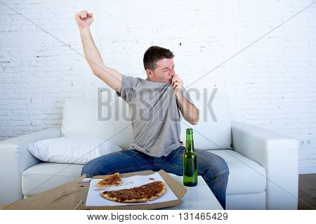 young man watching football game on television celebrating goal crazy happy on sofa couch at home with ball beer bottle and pizza looking excited and cheerfull kissing his team shield