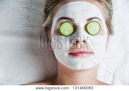 Portrait of beautiful spa girl with facial mask and cucumber. Beauty healthcare.