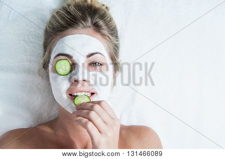 young woman with facial mask biting on a cucumber spa comcept