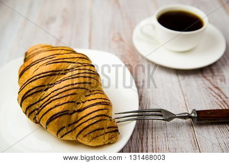 Croissant on a white plate and a cup with