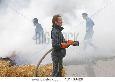 STOCKHOLM SWEDEN - MAY 14 2016: Women with water hose and men jumping over fire and smoke in the obstacle race Tough Viking Event in Sweden April 14 2016