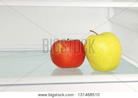 Yellow and red apple in domestic refrigerator taken closeup.Healthy lifestyle.