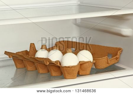Eggs in a paper box on refrigerator shelf taken closeup.