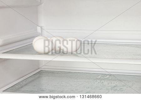 Fresh chicken eggs on refrigerator shelf taken closeup.