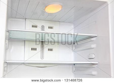The photo of open empty refrigerator taken closeup.