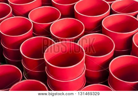 Rows of red flower ceramic pots on the shelves