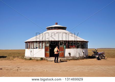 BAOTOU CHINA - OCTOBER 2 2012: Unidentified woman in front of permanent yurt in Xilamuren Grassland area. Xilamuren Grassland is one of the must-see attractions in Inner Mongolia.