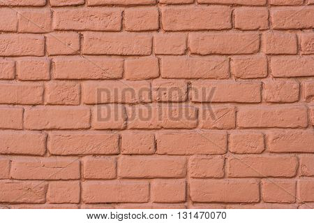 The texture of the brick wall that is painted red.