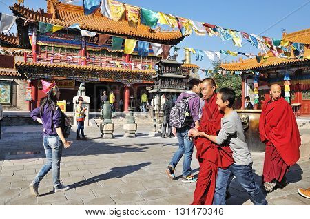 HOHHOT CHINA - OCTOBER 1 2012: Tourists and a novice monks in front of the Da Zhao Temple the temple is a Buddhist monastery and the largest temple in the city of Hohhot.