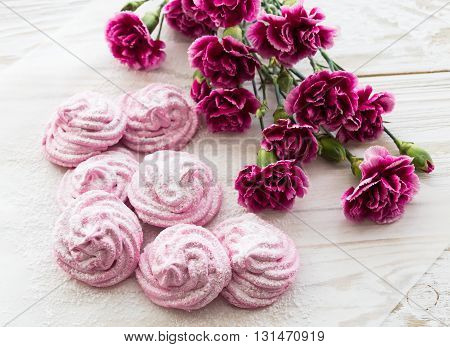 Homemade marshmallow dessert with carnations on wooden table