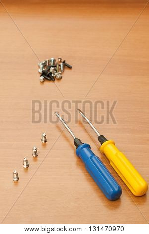 Yellow and blue screwdriver with screws on a wood background.