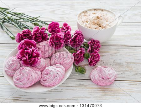 Homemade marshmallow dessert with carnations and cappuccino