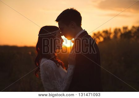 Silhouette of a loving couple on the background of the setting sun.