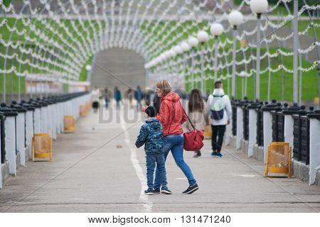 People on a pedestrian bridge in the Gulf city of Cheboksary Chuvash Republic Russia. 05/20/2016