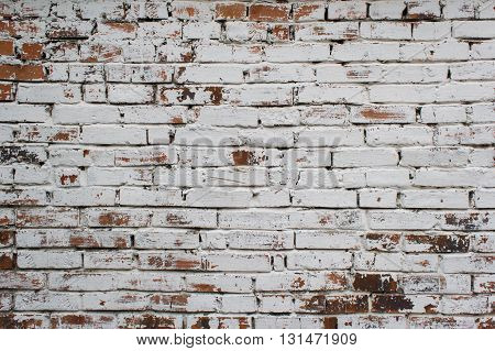Dilapidated brick wall painted in white color.