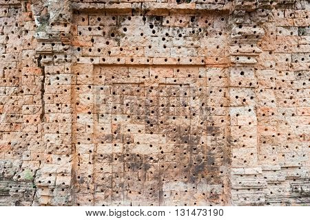 Wall with holes to hold the stucco decoration Angkor temples complex Siem Reap Cambodia