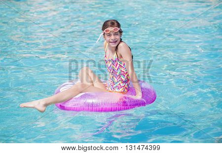 Beautiful young girl playing in the pool in summer time. Lots of copy space and water
