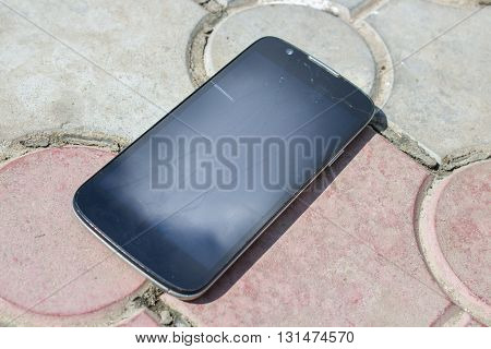 Cracked mobile smartphone smashed by a stone greyscale with blue