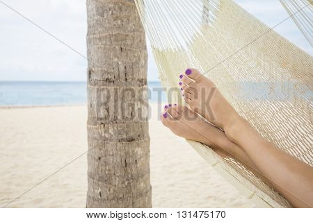 Beautiful female feet in a hammock on the beach at a tropical island resort