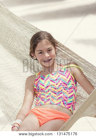 Cute Smiling little girl with braces relaxing in a hammock on a beach vacation at a luxury tropical island resort