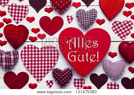 Red Heart Texture With German Text Alles Gute Means Best Wishes. White Wooden Background. Textile Hearts Which Are Dotted and Striped. Greeting Card For Birthday Wishes