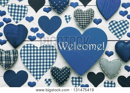 Blue Heart Texture With English Text Welcome. White Wooden Background. Textile Hearts Which Are Dotted and Striped. Greeting Card As Invitation