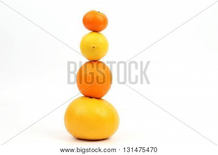 citrus fruit stand vertically on each other on white background