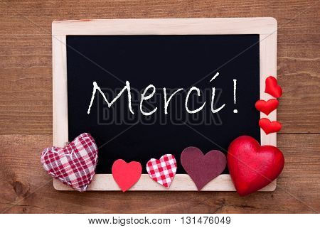 Blackboard With French Text Merci Means Thank You. Red Textile Hearts. Wooden Background With Vintage, Rustic Or Retro Style.