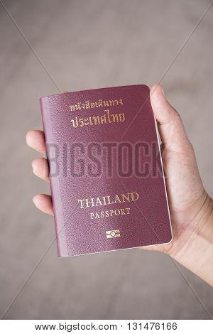Hand holding a Thailand Passport. (Non Logo)