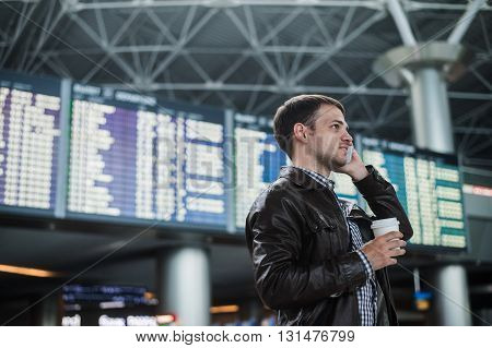 Smiling young traveller man at the airport talking on the phone in front of timetable board.