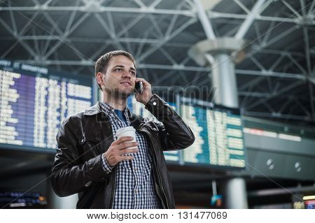 Cheerful man on the mobile phone in hall station in front of Board schedules.