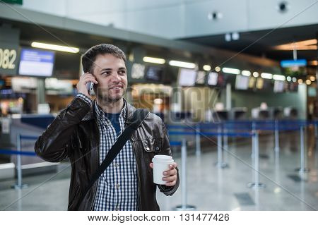 Portrait of young handsome man in 20s walking in modern airport terminal, talking on smart phone, travelling with bag, wearing casual style clothes, blurred registration desks on background.
