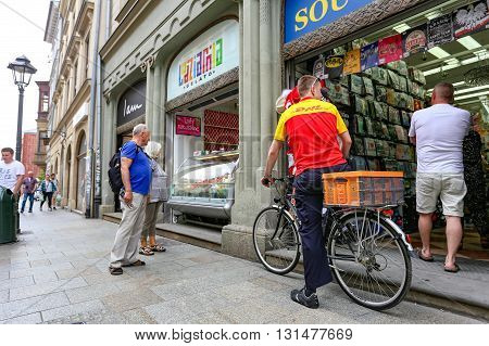 Krakow, Poland- May 25, 2016: DHL Delivery on the main market on the bike. on street