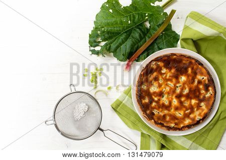 cake or pie on a green kitchen towel rhubarb stalk and leaf and a sieve with powdered sugar on a white painted wooden table view from above copy space background fades to white