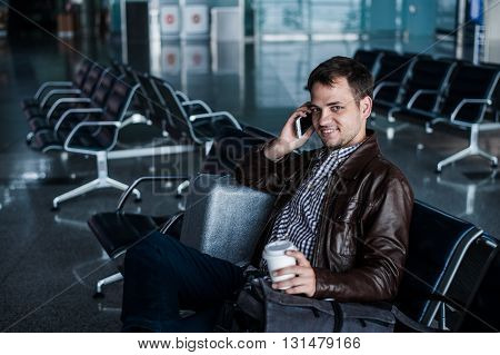handsome young man with black hair working, sitting on a chair things at the airport waiting for his flight.