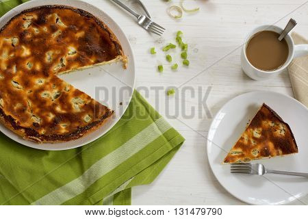 homemade cake or pie with rhubarb whole and serving green kitchen towel and a coffee cup on a white painted wooden table view from above
