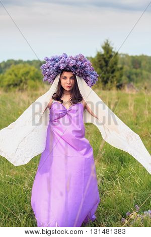 Beautiful young girl in a lilac dress with a wreath of lilac in the field. Her arms stretched out to the side