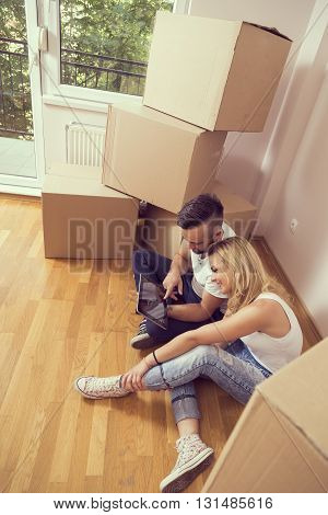 Young couple in love moving in a new appartment sitting on the floor planning to redecorate their new home