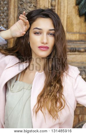Sexy young brunette woman in dress and pink coat, against the background of an old wooden door
