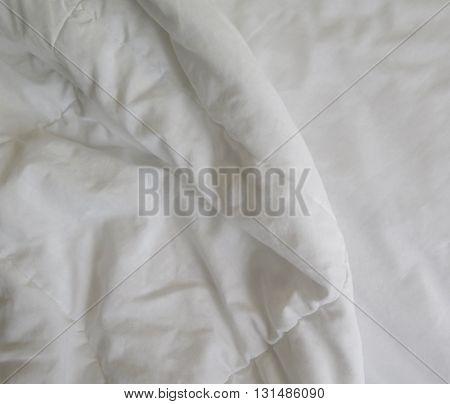 Detail of bed with set of white morning bedding
