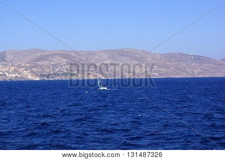 Long shot of a small sailboat that travels in the big blue sea and approaches an island.